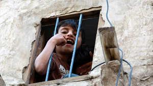 طفل يمينى يطل من نافذة منزل تقليدي في صنعاء التي تشهد قصفا لمواقع الحوثيين من قبل طائرات التحالف الذي تقوده المملكة العربية السعودية، 30 مارس/ آذار 2015