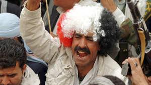 متظاهر في صنعاء يرتدي شعرا مستعارا بلون العلم اليمني في تظاهرة ضد عاصفة الحزم ، 3 مارس/ أبريل 2015