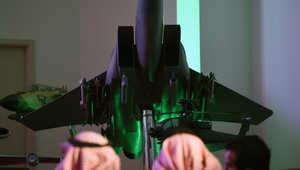 صحفيون سعوديون بجانب نسخة من طائرة مقاتلة للقوات السعودية خلال مؤتمر صحفي عن عملية عاصفة الحزم