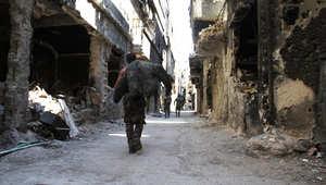 رجال يسيرون بين البنايات المدمرة في مخيم اليرموك في العاصمة السورية دمشق، 6 أبريل / نيسان 2015