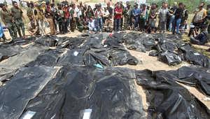 """عراقيون يشاهدون الجثث التي تم انتشالها من مقابر جماعية، لاشخاص يعتقد أنهم ضحايا مذبحة سبايكر التي ارتكبها تنظيم """"داعش""""، تكريت 12 أبريل/ نسيان 2015"""