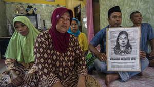 عائلة الخادمة الإندونيسية التي أعدمت في السعودية، ستي زينب، يحملون صورة لها في منزل العائلة في جاوة الشرقية، 15 أبريل/ نيسان 2015