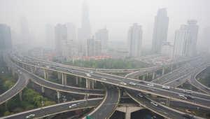 سيارات تعبر في طرق متعددة الطوابق في مدينة شانغهاي ويبدو تلوث الجو واضحا