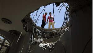 يمنيان ينظران من فتحة خلفتها غارة جوية على سطح مبنى قرب قاعدة فج عطان العكسرية التي تتمركز فيها كتيبة الصواريخ التابعة للحرس الجمهوري، 21 أبريل/ نيسان 2015
