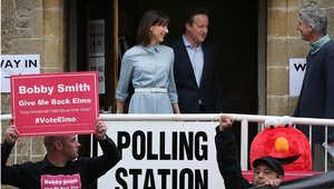 رئيس الوزراء البريطاني ديفيد كاميرون وزوجته سامانثا خلال خروجهما من مركز الاقتراع بعد تصويتهما في الانتخابات العامة، 6 مايو/ أيار 2015