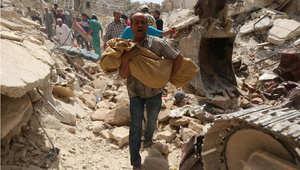 سوري يحمل جثة تم انتشالها من بين أنقاض مبنى تعرض للتدمير بقصف بالبراميل المتفجرة في حي قاضي عسكر بمدينة حلب 20 مايو/ أيار 2015