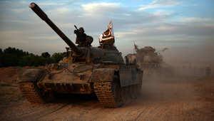 عناصر من المعارضة السورية تقود دبابات استولت عليها من القوات النظامية