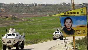 آليات لقوات اليونيفيل تمر قرب صورة لمقاتل من حزب الله بالقرب من مرجعيون في جنوب لبنان