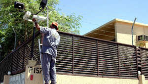 فني يضع كاميرا على السياج المحيط بمجمع سكني للأجانب العاملين في ميناء جدة على البحر الاحمر