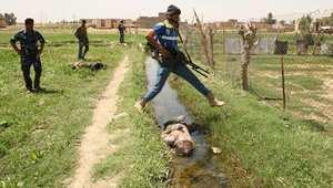 أحد الجنود التابعين للحكومة يقفز عن جثة مقاتل يعتقد أنه من داعش في الرمادي 26 أبريل/ نيسان 2014