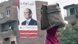 امرأة مصرية تمشي على طريق في الفيوم وفي خلفية الصورة لافتة للمرشح الرئاسي عبد الفتاح السيسي