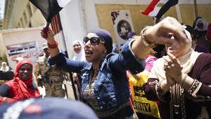 امرأة مصرية ترقص خلال انتظارها للتصويت في مركز اقتراع في حي عين شمس بالقاهرة