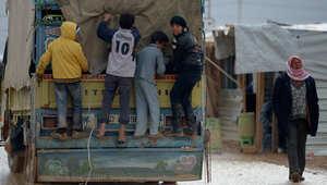 أولاد سوريون يقفون على الجزء الخلفي من شاحنة في المخيم