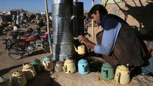أفغاني يحضر الشاي لزوار سوق المواشي في كابول بأفغانستان