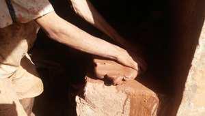 أحد الحرفيين يقوم بعجن الطين قبل صنع أشكال منه