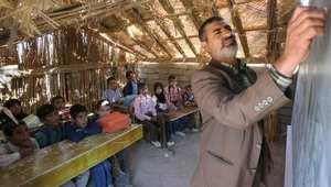استاذ عراقي يدرس الطلبة في صف بني من القطوب والقصب قرب مدنية الناصرية جنوب العراق - أرشيف - 2007