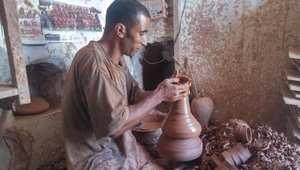 حرفي يقوم بصناعة الشكل الذي يريده على آلة اللولب التقليدية