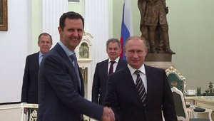 مؤيد للأسد يحمل صورة الرئيسين السوري والروسي
