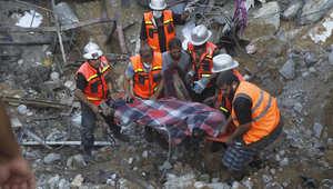 عمال إغاثة يرفعون جثة أحد أفراد عائلة قضت في قصف بخانيونس