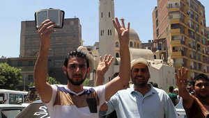 عدد من أنصار جماعة الإخوان المسلمين يرفعون شعار رابعة في الذكرى الأولى للعملية العسكرية ضد مؤيدي الجماعة