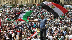 متظاهر مصري مصري يحمل العلم المصري والعلم الفلسطيني في ميدان التحرير بالقاهرة في 13 مايو 2011