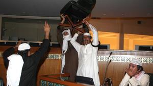 رجل كويتي يحمل كرسيا أثناء اقتحام قاعة عبدالله السالم في مجلس الأمة الكويتي يوم 16 نوفمبر 2011