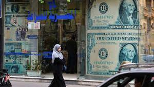 مرأة مصرية تمشي أمام محل صرافة في العاصمة القاهرة