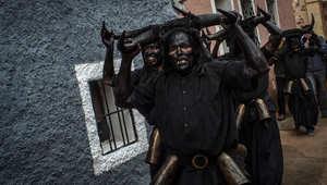 أشخاص يغطون وجوههم بالنفط ويحملون قرون ثيران يشاركون في مهرجان الشياطين والأقنعة في اسبانيا