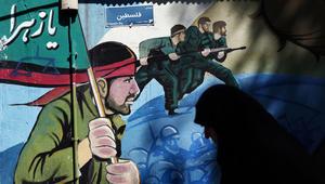 امرأة إيرانية تمشي بجانب جدارية تظهر جنود إيرانيين أثناء الحرب العراقية الإيرانية، بعد مظاهرة للتنديد بالتحالف العسكري الذي تقوده السعودية في اليمن