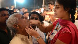 متطوعة تدخل السمكة في فم مريضة