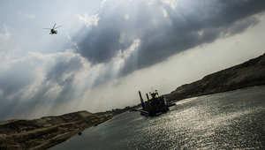 مروحية تابعة للجيش المصري تحلق فوق حفارة تعمل على الممر المائي الجديد لقناة السويس