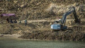 عمال على ضفاف مجرى قناة السويس الجديدة