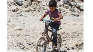 """طفل سوري يقود دراجته في عين العرب """"كوباني"""" بين الأنقاض التي خلفتها الحرب مع داعش، 20 يونيو/ حزيران 2015"""