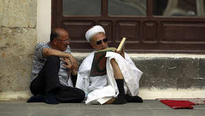 يمني يتلو القران أمام أحد المساجد بصنعاء في بداية شهر رمضان