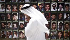بحريني يمر من أمام لوحة تضم صورا لمعتقلين شاركو في الاحتجاجاب بالبحرين 10 يوليو/ تموز 2015