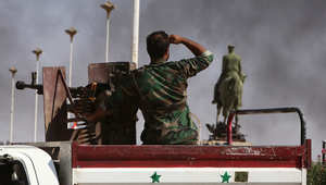 جندي من قوات النظام السوري يراقب الدخان بالقرب من تمثال باسل الأسد في مدينة الحسكة