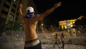 متظاهر لبناني أمام الأسلاك الشائكة التي تفصل بين المتظاهرين والقصر الحكومي في نهاية مظاهرة حاشدة ضد الطبقة السياسية في لبنان
