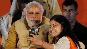 """فتاة تأخذ """"selfie"""" مع مودي، في تجمع انتخابي في مومباي يوم 21 أبريل 2014"""