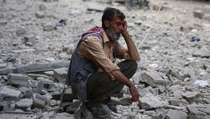 رجل سوري وسط أنقاض مبان مدمرة بعد ضربات جوية لقوات النظام في منطقة يسيطر عليها المتمردون في دوما