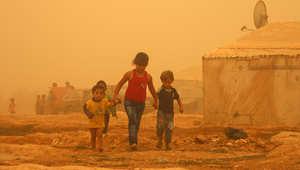 أطفال سوريون أثناء العاصفة الرملية في مخيم للاجئين على مشارف مدينة بعلبك شرق لبنان