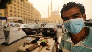 """ناشط لبناني ضمن حملة """"طلعت ريحتكم"""" يضع قناعا بسبب عاصفة رملية تهب على بيروت"""