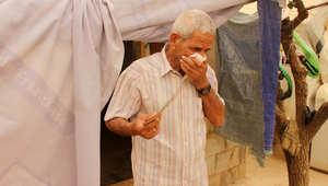 لاجئ سوري يغطي وجهه ليحمي نفسه من الغبار أثناء عاصفة رملية في مخيم للاجئين بالقرب من تعلبايا