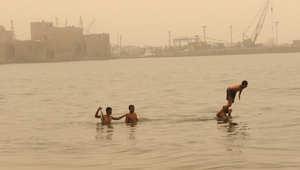 لبنانيون يسبحون بالقرب من قلعة صيدا أثناء عاصفة رملية في مدينة صيدا جنوبي لبنان