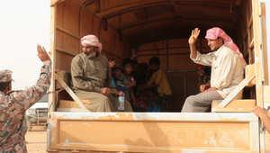 لاجئون سوريون يجلسون في الجزء الخلفي من شاحنة تابعة للجيش الأردني
