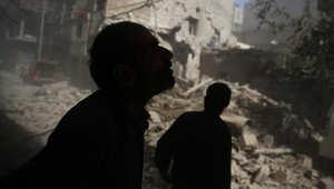 سوريون ينظرون إلى الأضرار التي سببتها الغارات الجوية على المنطقة التي يسيطر عليها المتمردون بدوما في 2 أكتوبر 2015