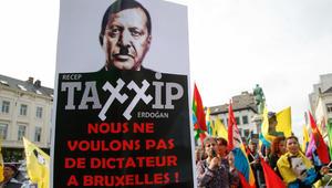 """لافتة تظهر أردوغان مكتوب عليها """"لا نريد دكتاتورا في بروكسل"""" حيث يطلق المشاركون هتافات احتجاجا على الهجمات ضد الاكراد من قبل النظام التركي"""