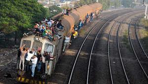 صورة لرجال جالسين على سطح قطار مكتظ أثناء سفرهم في العاصمة المصرية القاهرة