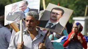 رجل سوري يرفع صورتين للأسد وبوتين بالقرب من السفارة الروسية في دمشق
