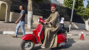 """صورة لرجل مصري يركب دراجة نارية في القاهرة ويرتدي """"الطربوش"""" التقليدي"""