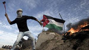 متظاهر فلسطيني يقذف حجرا باتجاه القوات الإسرائيلية قرب البريج في وسط قطاع غزة